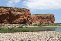 red cliffs and pebbles on the beach